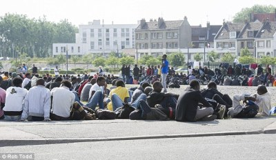 Huddled in the sun=Africans from the Jungle 2 camp in Calais, France wait for food handouts